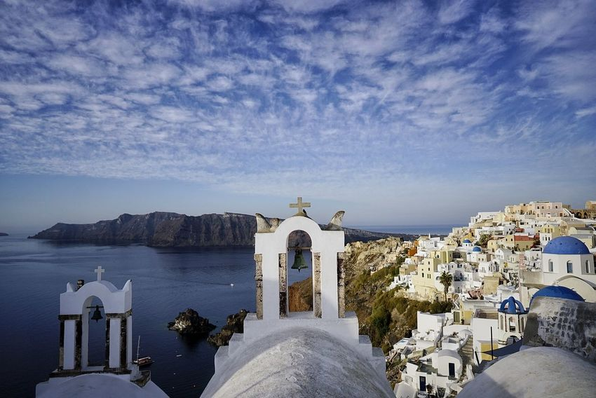 Religion Architecture Dome Travel Destinations Summer Spirituality Town Whitewashed No People Sea Water Sky Outdoors Day Urban Skyline Santorini, Greece Place Of Worship Vacations Clear Sky Cross Low Angle View Architectural Column First Eyeem Photo Streetphotography