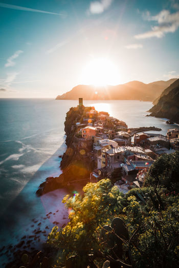 Vernazza, italy. high angle view of townscape by sea against sky during sunset