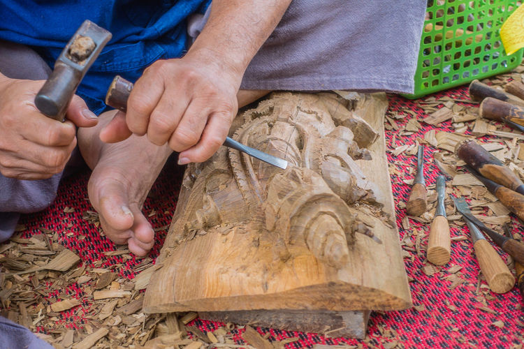 Hands of the craftsman wooden carving a bas-relief. Adult Art And Craft Carving - Craft Activity Close-up Craftman Day Handicraft Handmade Human Body Part Human Hand Men Occupation One Person Outdoors People Skill  Work Tool Working Workshop