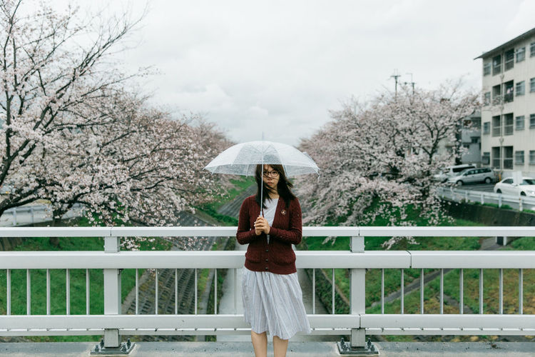Portrait Of Young Woman With Umbrella On Bridge Against Cherry Trees