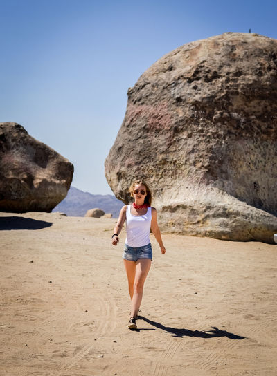 Full length portrait of a woman on rock