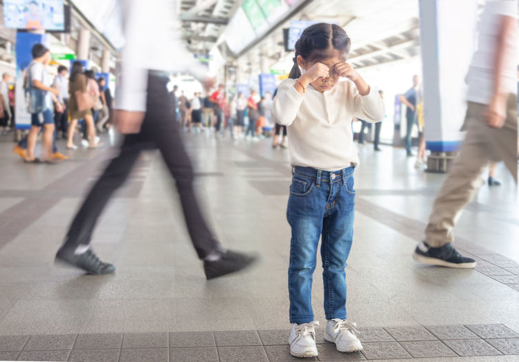 Full length of girl crying while standing on railroad station platform