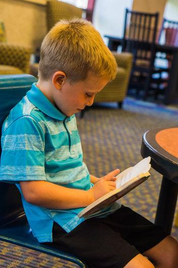 Cute boy reading menu at restaurant