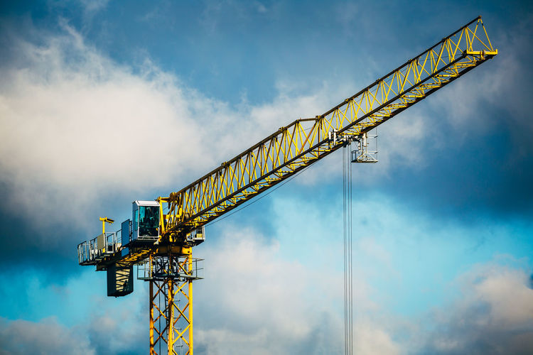 Construction crane against cloudy blue sky.