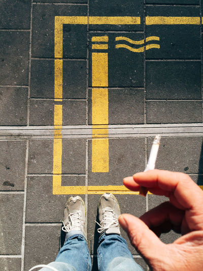 Low section of man smoking cigarette on footpath