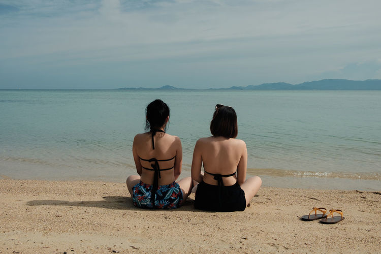 Rear View Of Female Friends In Bikini Sitting On Shore At Beach Against Sky