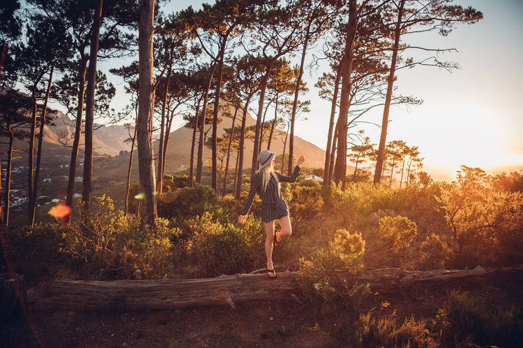 Woman standing against trees during sunset