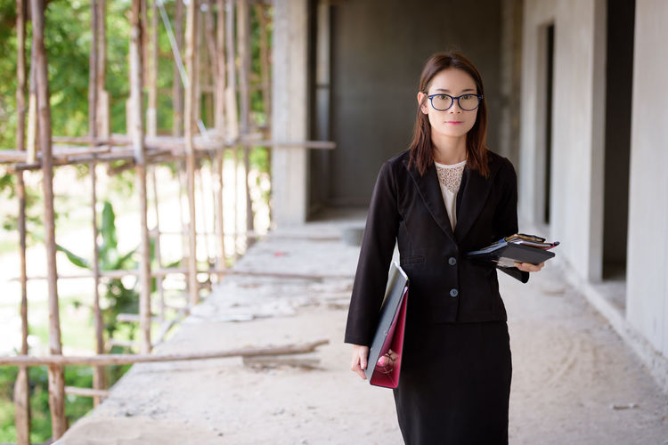Portrait of young businesswoman with file standing in incomplete building at construction site