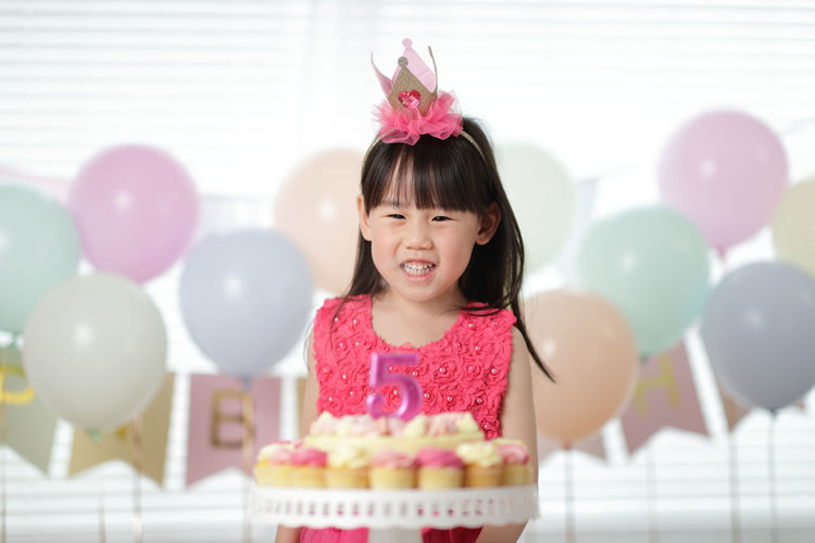 Portrait of smiling girl with pink balloons