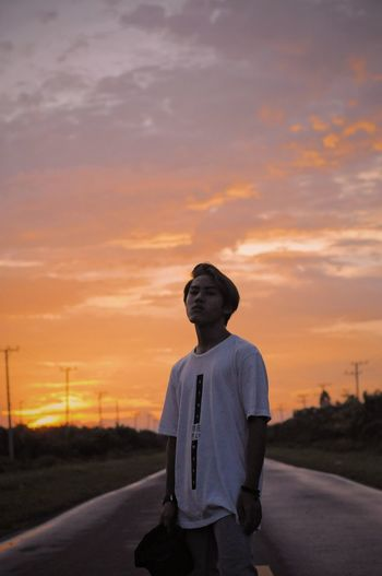 Portrait of boy standing on road against sky during sunset