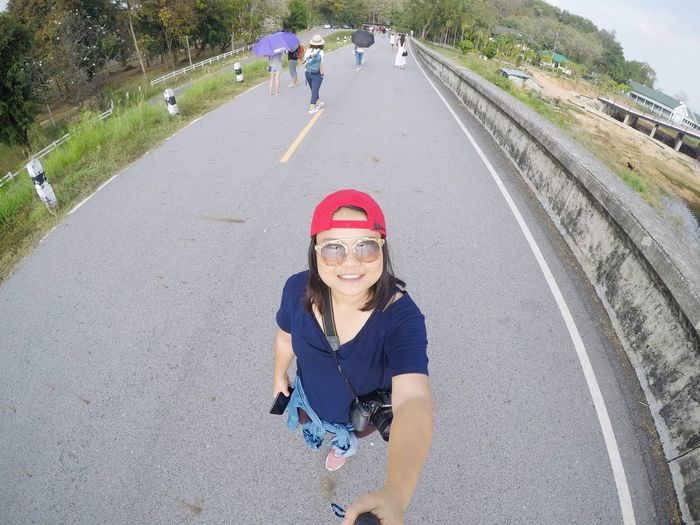 High angle portrait of smiling woman standing on road