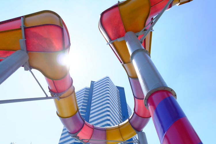 Low angle view of colorful slide against clear sky during sunny day