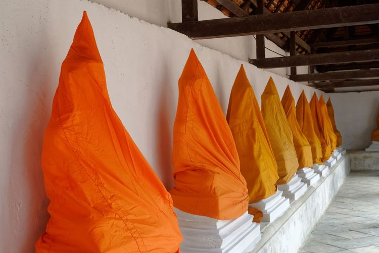 Statues covered with orange fabrics in buddhist temple