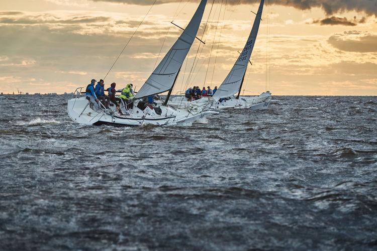 People sailing in sea against sky during sunset