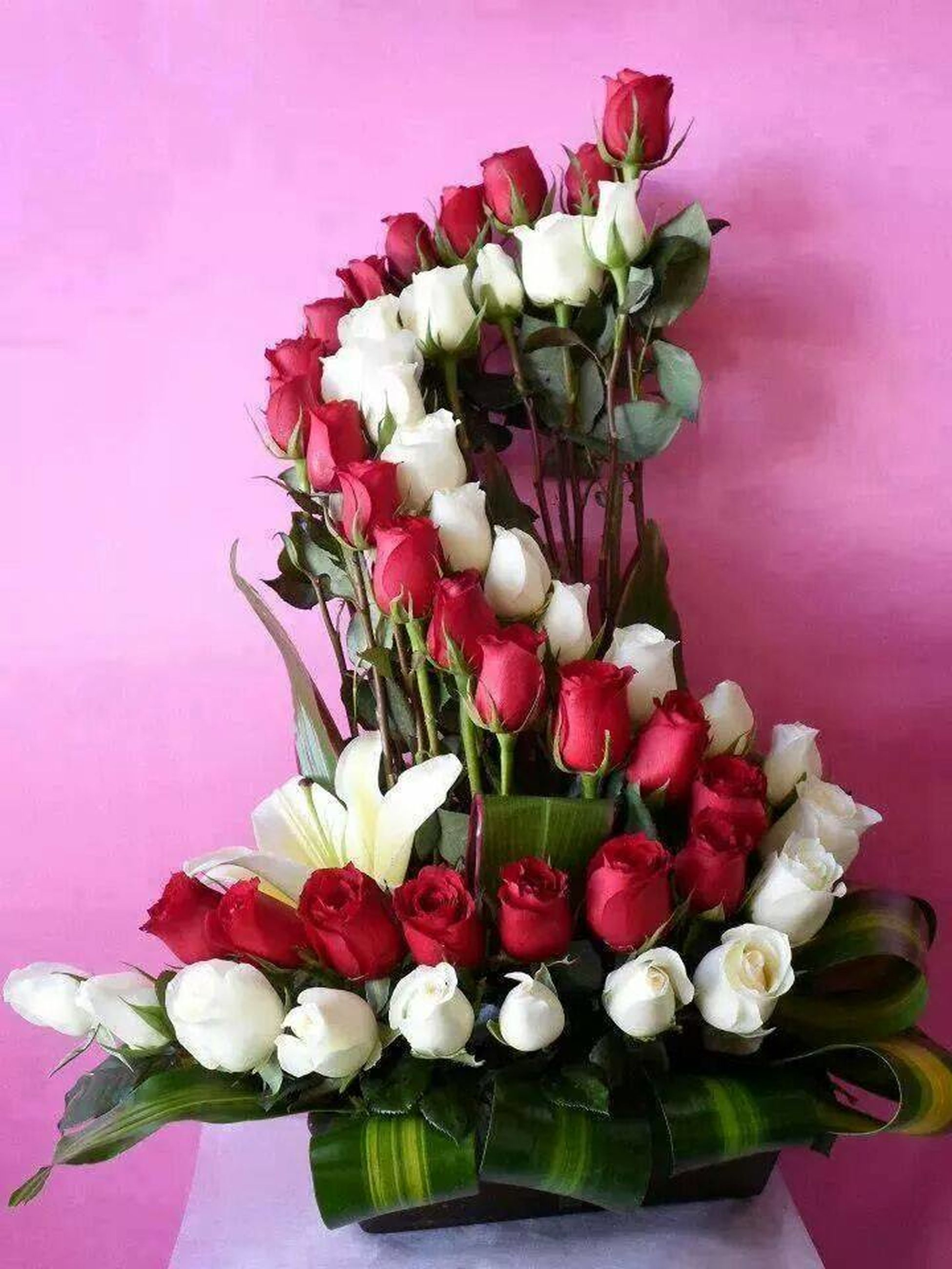 flower, freshness, fragility, petal, indoors, flower head, vase, beauty in nature, growth, pink color, tulip, plant, nature, leaf, decoration, potted plant, table, bouquet, wall - building feature, flower arrangement