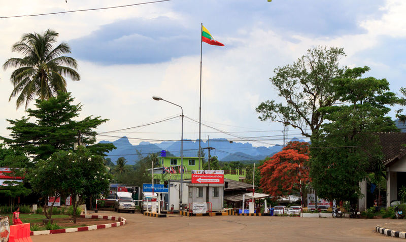 The border between Thailand and Myanmar Architecture Border Building Exterior Built Structure Cloud - Sky Day Flag Flag Pole Immigration International Border Nature No People Outdoors Palm Tree Patriotism Sky Travel Traveling Tree