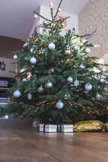 Illuminated christmas tree on floor at home