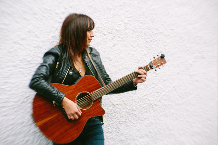 Mature woman playing guitar against white wall