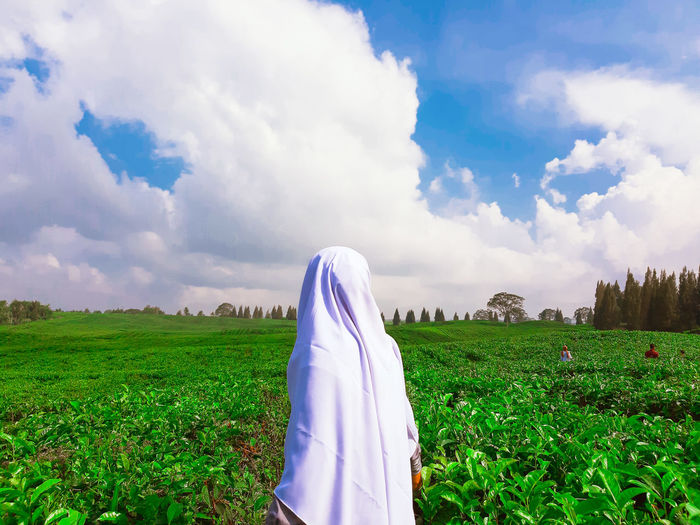 Woman wearing headscarf standing amidst plants against cloudy sky