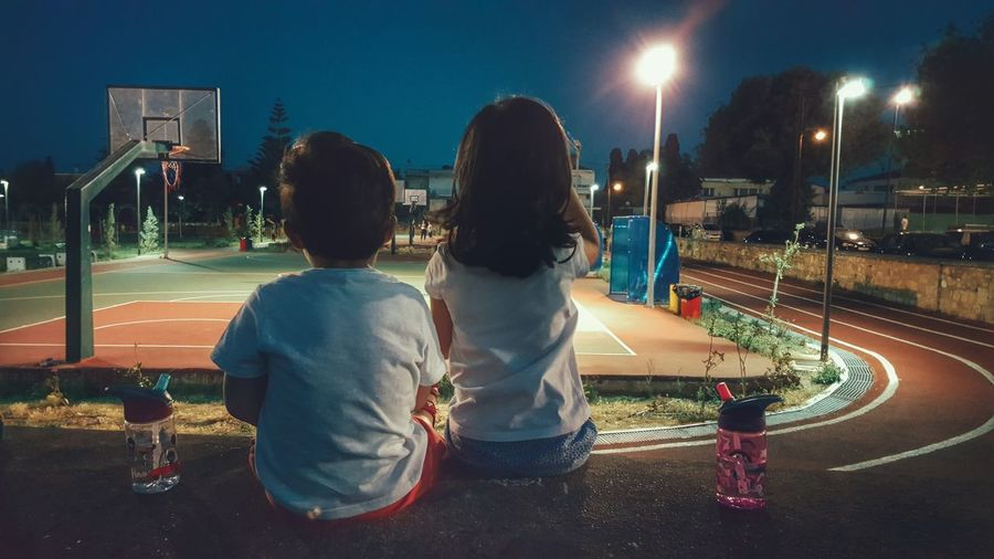 Rear view of kids sitting on retaining wall looking at illuminated basketball court