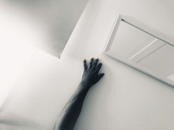 High angle view of hand touching wall at home