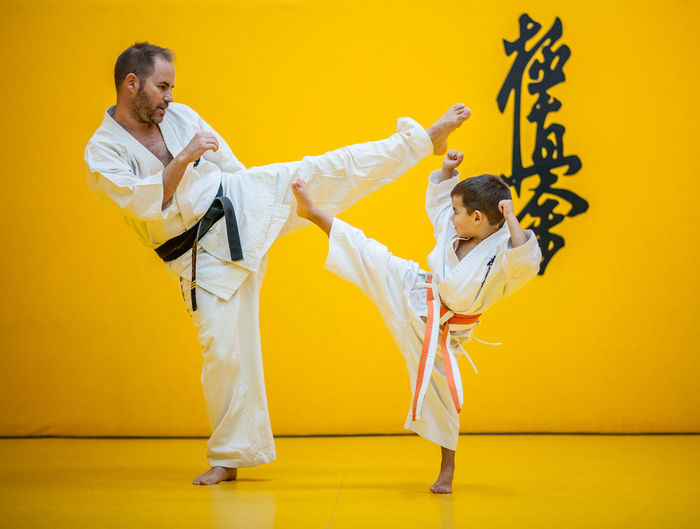 karate sensei with his student practicing high kick Two People Full Length Yellow Indoors  Martial Arts Men Lifestyles Colored Background Sport Adult People Young Adult Healthy Lifestyle Clothing Wall - Building Feature Real People Exercising Young Men Women Side View Human Arm