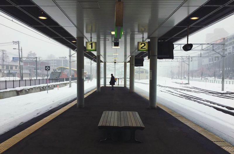Woman standing in railroad station during winter