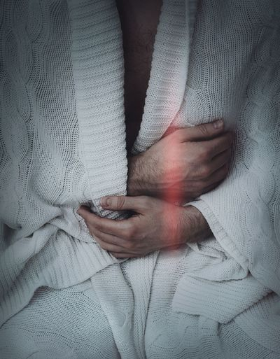 Midsection of man wearing white bathrobe
