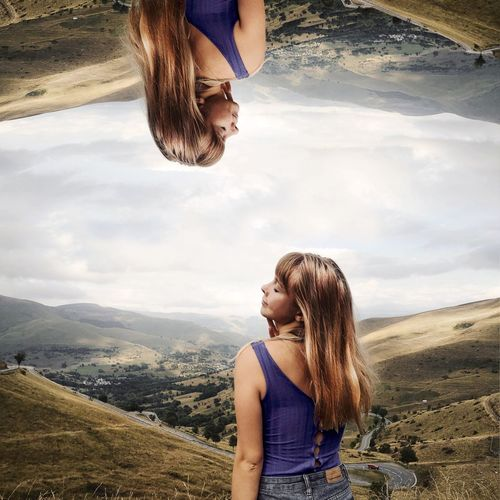 Young woman with arms raised against mountains