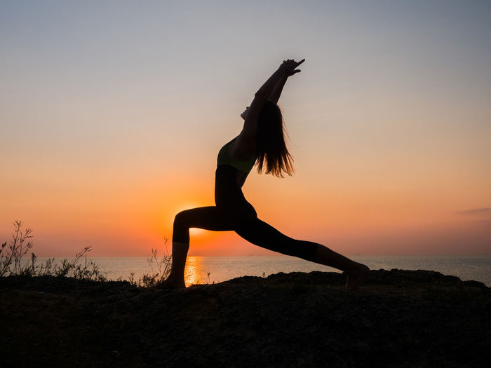 Side View Of Woman Doing Exercising On Field Against Sea During Sunset