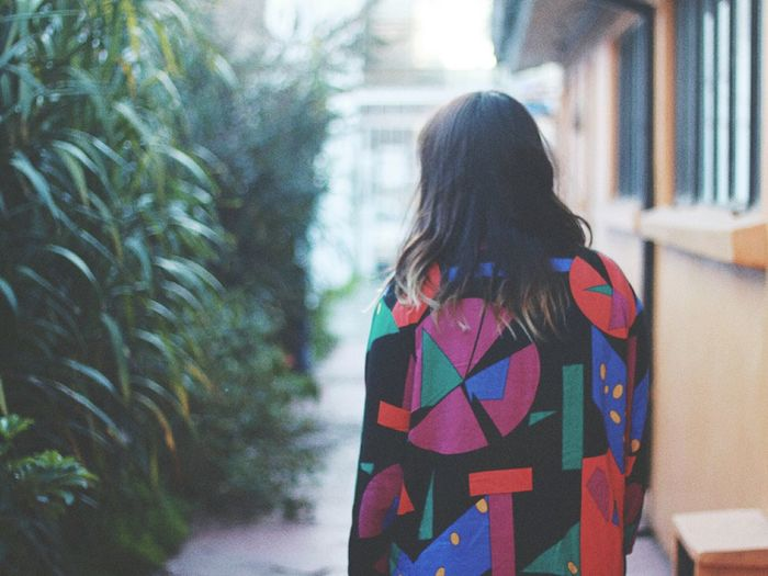 Rear View Of Woman In Patterned Clothing Standing By Building
