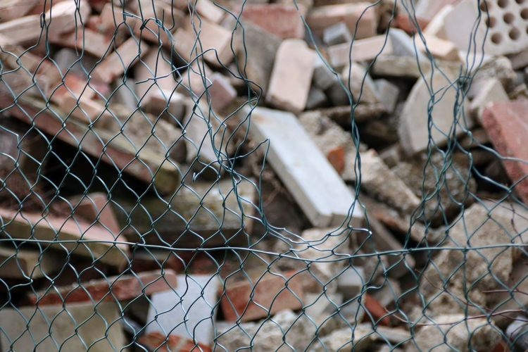 Hole In Fence Stone Rubble Stone Material Stones EyeEm Selects Trapped Destruction Close-up Barbed Wire Chainlink Fence Barricade Chainlink Fence Broken Wire Mesh