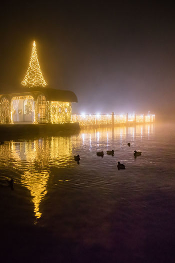 Illuminated mosque in lake against sky at night