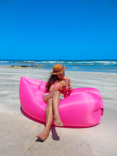 Woman with pink umbrella on beach