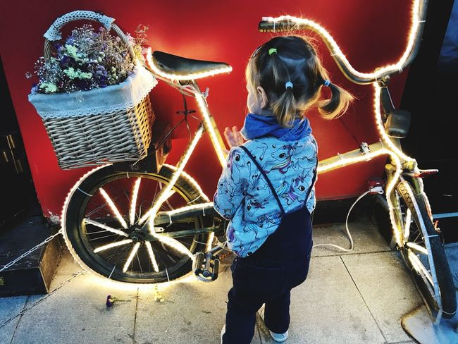 Night Lights Lights Happy Child  Beauty In Ordinary Things Real People One Person Casual Clothing Women Day Females Lifestyles Child Childhood Rear View Standing Transportation Mode Of Transportation Three Quarter Length Outdoors Wheel