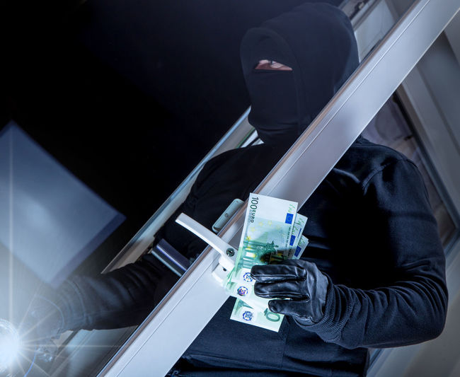 Close-up of robber with paper currency standing outdoors at night