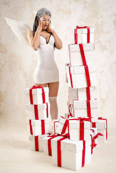 Young woman as angel with heap of gift boxes posing indoors Celebration Christmas Event Holiday Makeup Myth Presents Woman Angel Angel Wings Beautiful Woman Brunette Caucasian Conceptual Gift Boxes Gifts Indoors  One Person Real People Red Ribbon Sexygirl Standing Studio Shot Young Adult Young Women