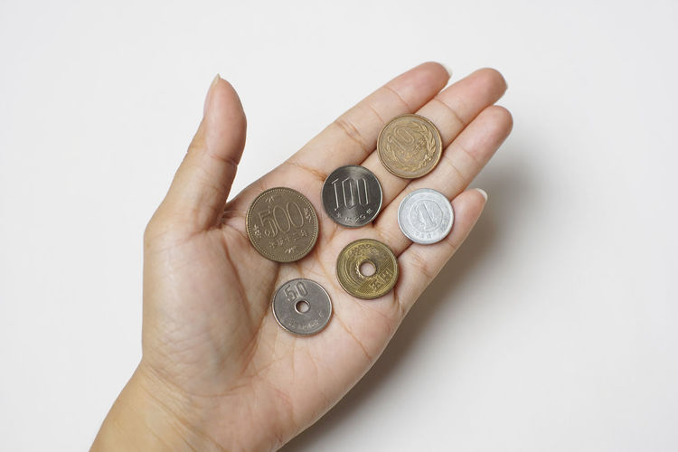 Close-up of hand holding coins over white background