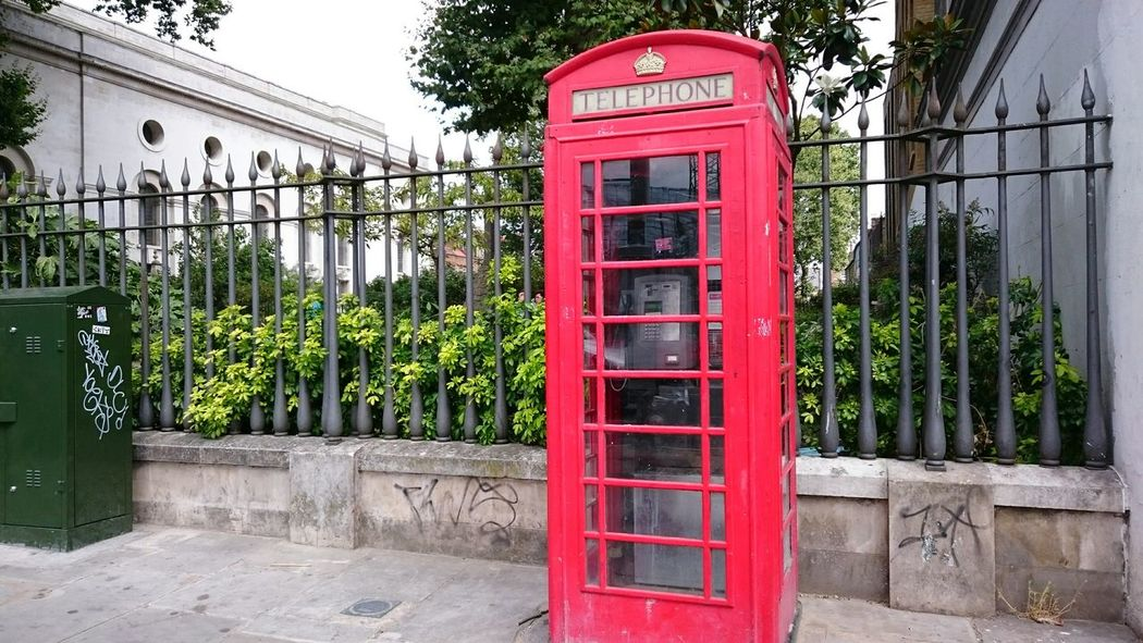 Outside Christ Church in Spitalfields, East London Phone Booth Architecture British Culture Railing City Connection Nature Tree Red Colour Phone Box Red Communication Telephone Box Telephone Historical Sights Famous Place EyeEm Best Shots Colour Of Life Focus On Foreground Eye4photography  No People EyeEm Gallery Capital Cities  Outdoors Hello World