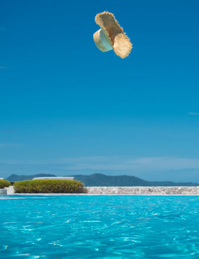 Swimming pool in sea against clear blue sky