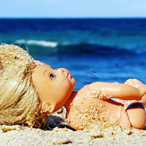 Close-up of doll lying on beach