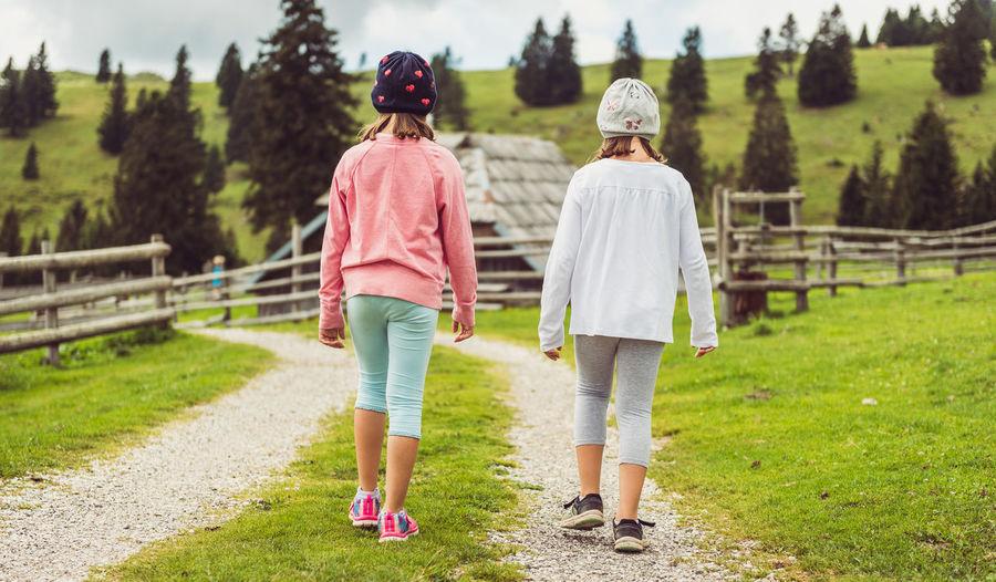 Rear view of women walking on grassland