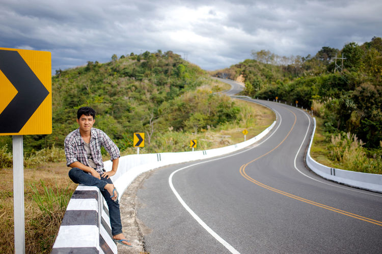 Portrait of man sitting on retaining wall by road against sky