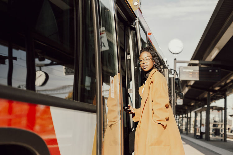 Woman standing on train in city