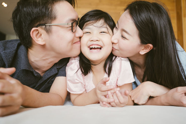 Asian Parents kissing their little daughter on both cheeks. family portrait. Asian  Family Happiness Happy Happy People Family Time Home House Daughter Parent Father Mother Dad Mom Love Lifestyles Living Room ASIA Japanese  Korean Thai Taiwan Smiling Smile Fun Portrait Girls Kissing Kiss