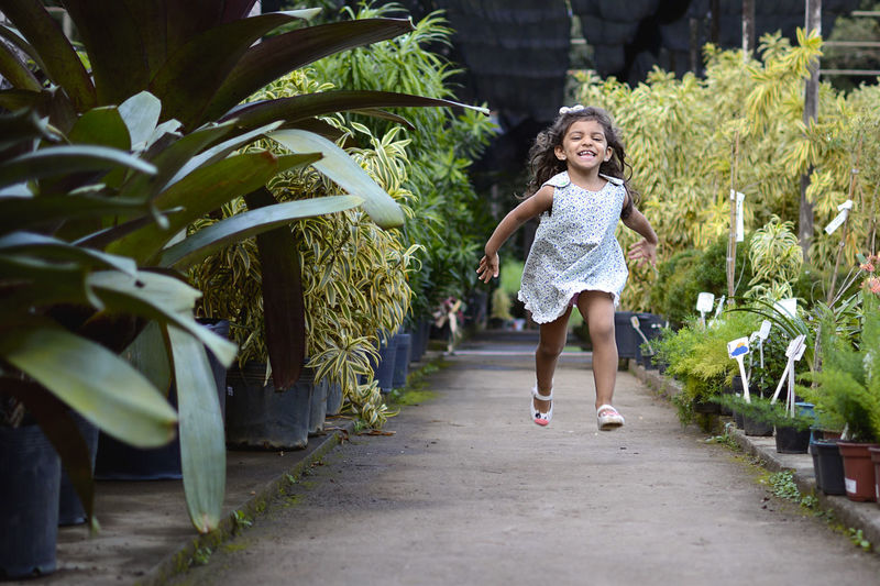 Full Length Of Cheerful Girl Running At Greenhouse