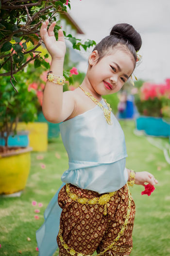 Little girl with Thai dress. Asian  Backyard Gold Makeup Slippers Thai Thai Uniform Thailand Accessories Asian Girl Asiangirl Blue Child Childhood Females Focus On Foreground Garden Girls Innocence Leisure Activity Lifestyles Loincloth One Person Outdoors Real People Thai Food Thai Style Women