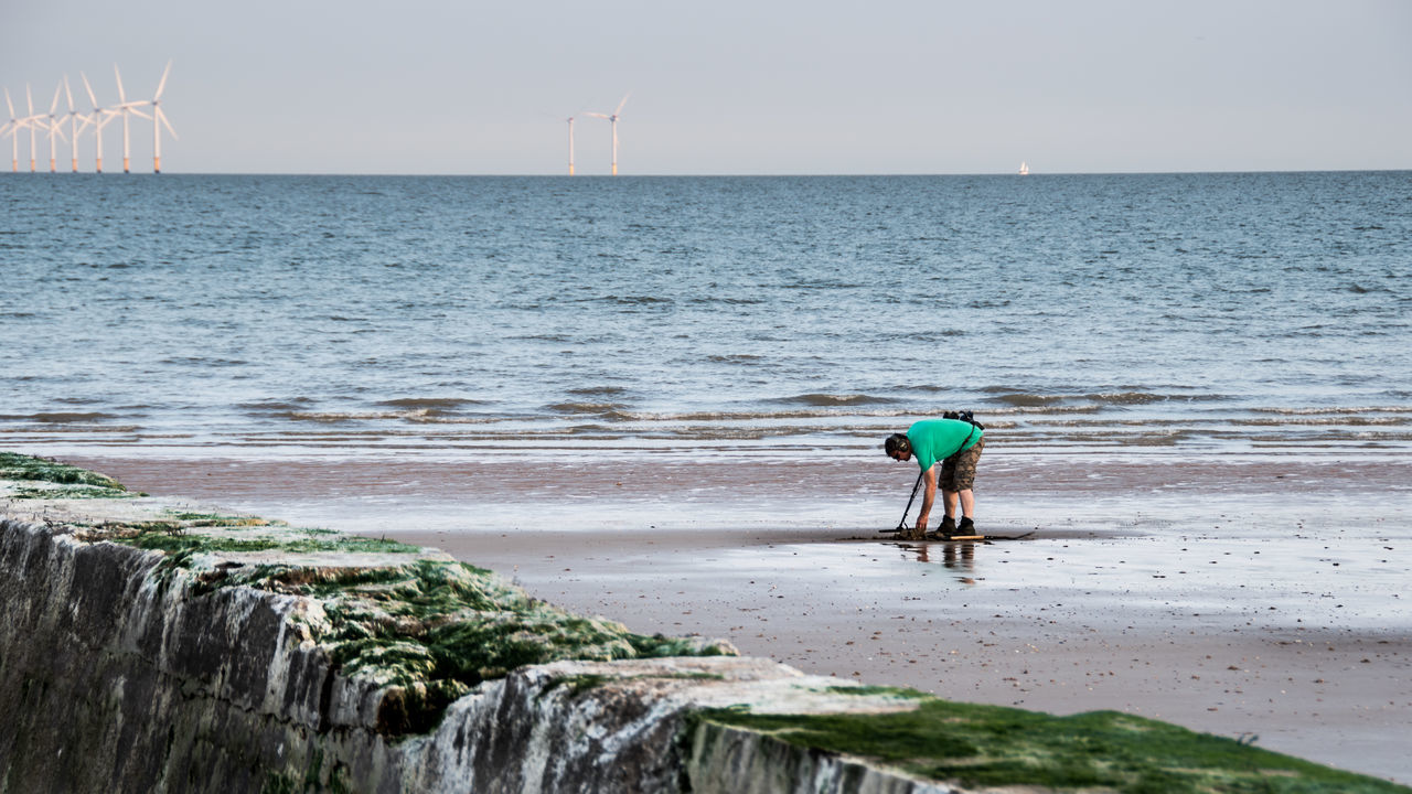 sea, water, real people, nature, shore, scenics, horizon over water, alternative energy, leisure activity, lifestyles, beach, wind turbine, day, one person, wind power, men, outdoors, beauty in nature, full length, sky, windmill, people