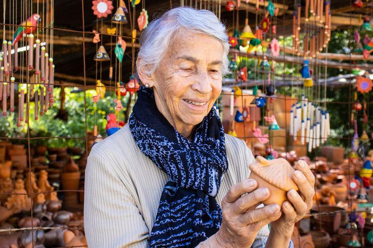 Senior woman holding souvenir at market stall
