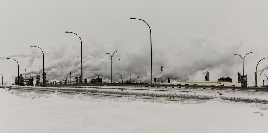 Street Lights By Road Against Cloudy Sky During Winter